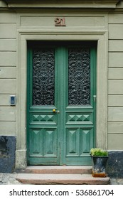 Old green door with glass windows leads to a grey house