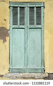 old green doors with peeling paint in yellow wall of house in medieval provence village of callas