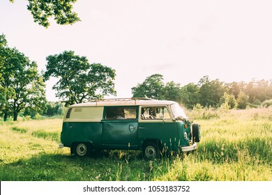 Old green hippy bus in green forest photographed at sunset