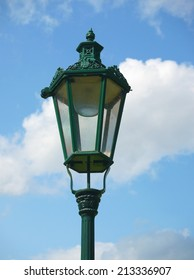 Old green metal lantern against blue sky