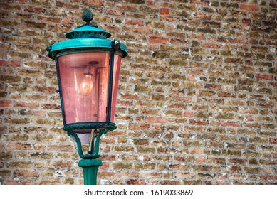 Old green metal with pink glass lantern against brick wall in Venice, Italy.in foreground