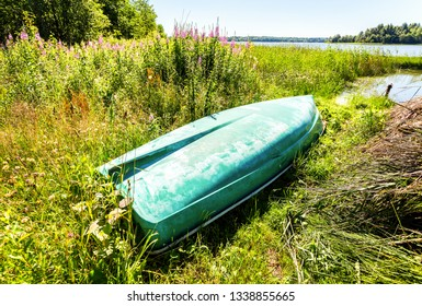 Old green plastic fishing boat on the bank of the lake in summer sunny day