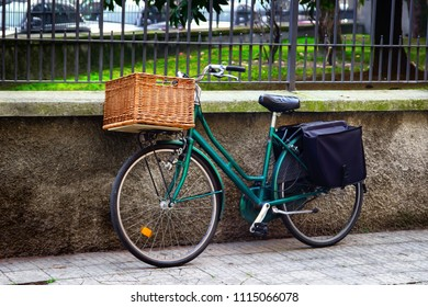 Old green retro bicycle with basket at street