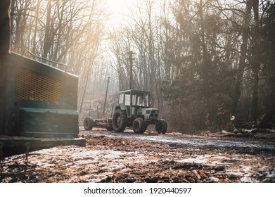 Old green tractor with trailer loaded with logs. Forestry tractor or forestry tractor for harvesting wood in the forest