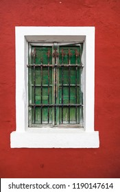 Old green window, red and white wall.