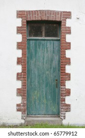 Old green wood door surrounded by brick wall