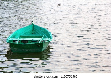 Old green wooden boat on the water, copy space