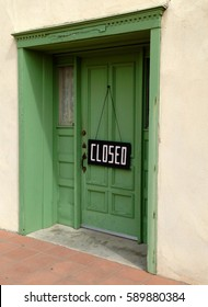 "Old green wooden door with ""closed"" sign"