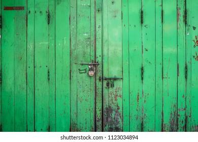 Old green wooden door with rusty key lock vintage texture background
