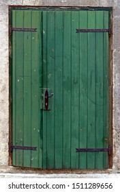 Old green wooden doors on stone wall