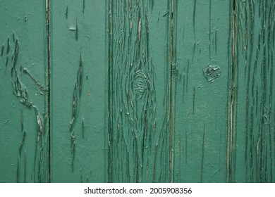 Old green wooden wall with cracked paint, background texture. High quality photo