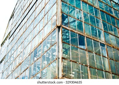 The old greenhouse with rusty windows and the blue sky on a background