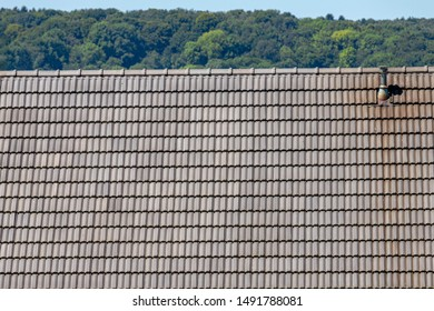 Old grey brick rooftop with chimney under blue sky and trees, Tiles background details, Shingles texture, Abstract geometric pattern, Roof brick material.