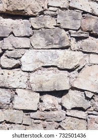 Old grey and brown rough stone wall, closeup texture background