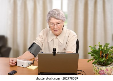 Old grey haired woman demonstrates how easy to monitor her blood pressure and pulse at home. All her vital signs are transmitted to telemedicine center, at the same time