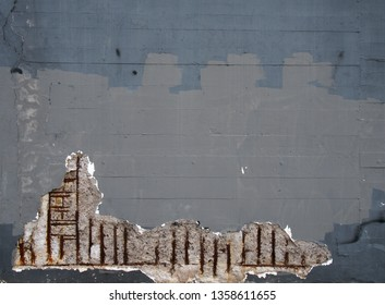 an old grey painted concrete wall with corroding rusty steel reinforcement bars causing damage to the structure