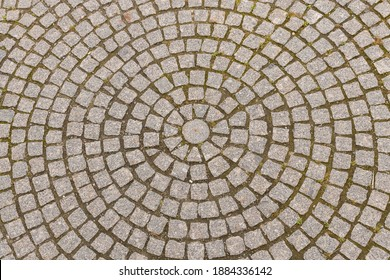 Old grey pavement of cobble stones in a circle pattern in an old medieval european town.