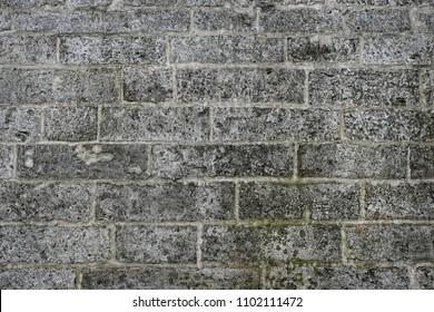 old grey stone wall. The masonry of stone wall, background