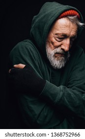 Old grey-bearded frozen tramp man with grey beard embracing himself to warm up posing over black background.