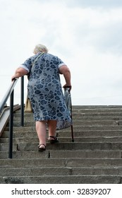 Old grey-haired the woman climbs the stairs by means of a crutch and a handrail