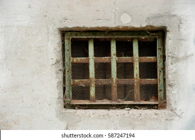the old grille on the window in the concrete wall