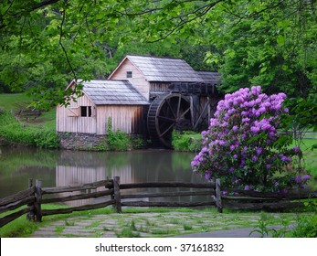 An old grist mill with a reflecting pond and spring flowers.