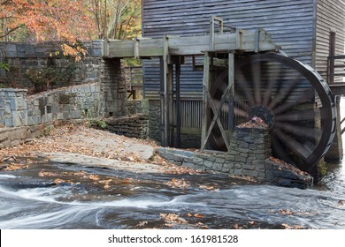 Old grist mill, with a water driven wheel to grind and a creek beside, flowing over stones