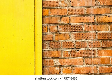 Old grunge brick wall texture with yellow metal detail.