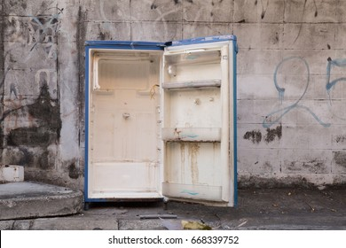 Old and grunge of crack or waste used refrigerator left on the street