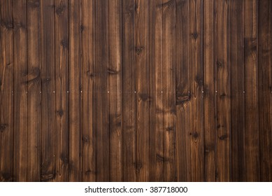 Old grunge dark brown wood panel pattern with beautiful abstract grain surface texture, vertical striped background or backdrop in architectural material decoration concepts, vintage or retro style