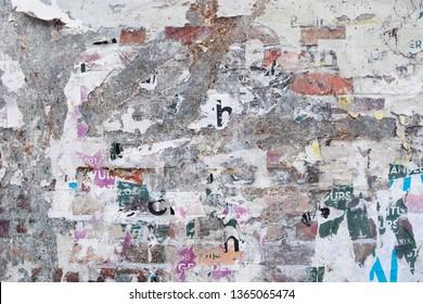 old grunge exposed brick wall with ripped weathered street poster bits