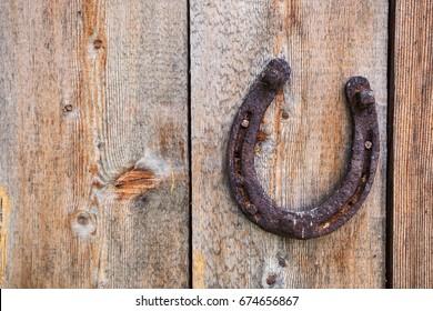 Old grunge horse shoe on wooden background