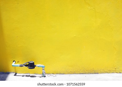 old grunge water meter with space yellow wall background.