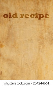 Old grunge wooden kitchen cutting board as background with words old recipe