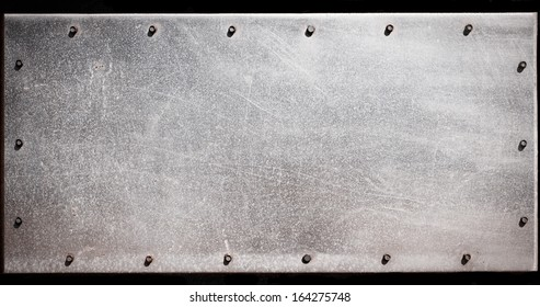 Old grungy, dirty and scratched metal plate with screws
