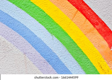 old grungy texture, dirty concrete wall with cracks. Different colors of the rainbow. Rainbow painted with paints on the wall.