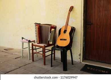 Old guitar and accordion on chairs against a wall background with crumbling paint and a door