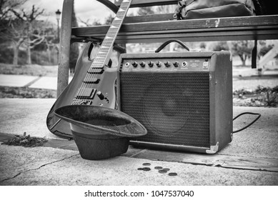 Old guitar and amplifier next to a park bench, a street music concept