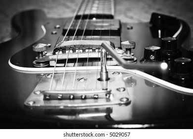 An old guitar in black-and-white colors. Shot with vignette effect