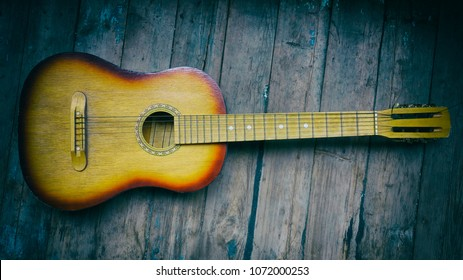 old guitar on a wooden background