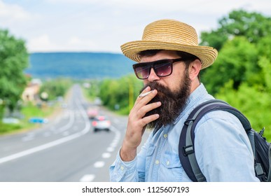 Old habit. Man with beard and mustache in straw hat smoking cigarette, road background defocused. Traveler stylish hipster take brake with cigarette. Smoking cigarette before long journey.