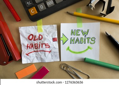 Old habits and new habits handwritten on white pieces of paper at the office