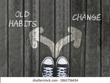 Old habits versus change written on asphalt road with selective focus on  two white arrows, dilemmas choice concept. Team building, motivation positive thinking