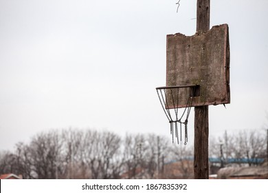 Old, half destroyed, rotten basketball backboard, in a decaying sports playground, standing during a cold winter.