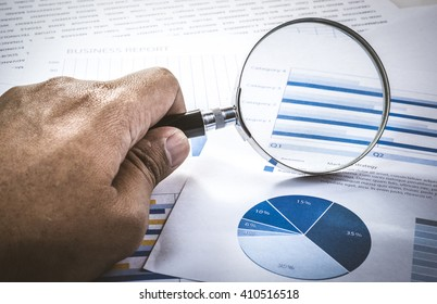 Old hand of businessman holding magnifying glass with diagram graph.For business market research concept