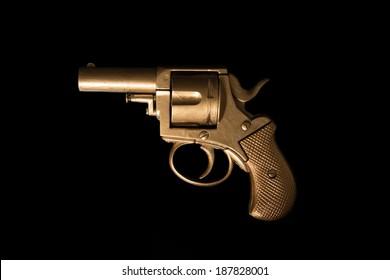 Old hand gun revolver with an aged golden patina displayed sideways on a dark background with copyspace