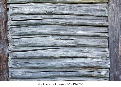 Old Hand Hewn Natural Log Cabin Wall Facade Fragment Texture. Rustic Log Wall Horizontal Timber Grey Background. Fragment Of Unpainted Gray Wooden Debarked Logs Barn Wall Wallpaper.  Planed House Wood