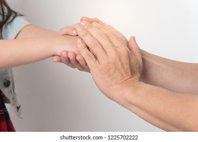 Old hand hold young hand together,chake hand and show concern,take care and give hope.
