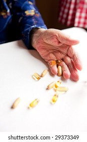 An old hand holding pills on a table