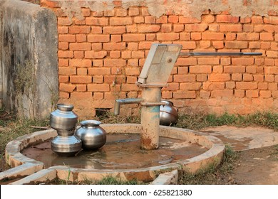 Old hand operated water pump and water containers in rural India